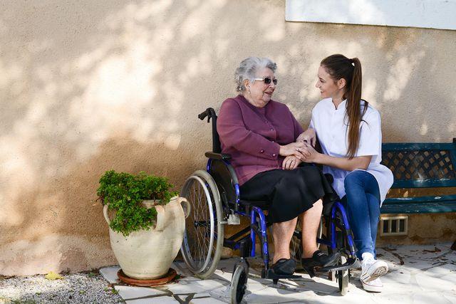 ältere Frau im Rollstuhl und Pflegekraft, die neben ihr auf einer alten blauen Parkbank sitzt. Beide sind zueinander gebeugt, lachen sich gegenseitig an und halten sich an den Händen.