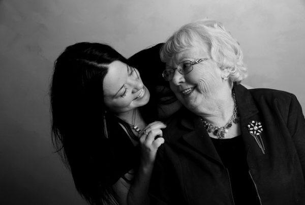 Großmutter an Enkelin angelehnt, die sich über ihre rechte Schulter beugt. Beide lachen sich an.