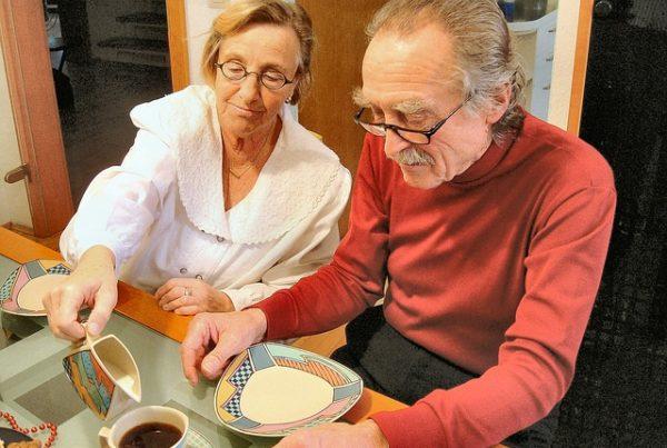 älterer Herr, der vor einem Teller und einer Tasse Kaffe sitzt. Daneben Helferin, die ihm Milch in den Kaffee einschenkt.