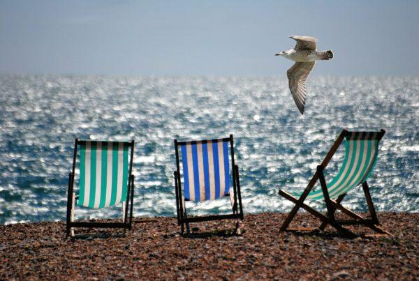 3 gestreifte Liegestühle, die in einer Reihe am Strand vorm Meer stehen. Möwe fliegt oben drüber.