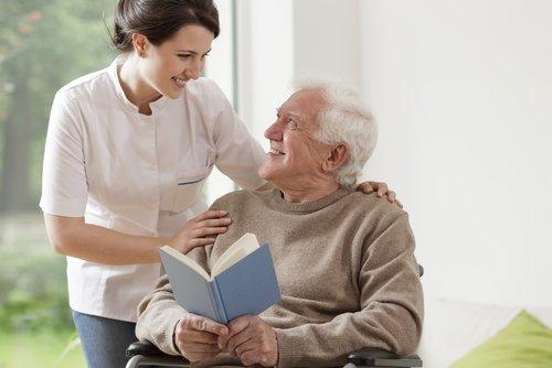 Pflegekraft hat Hände auf die Schultern eines im Rollstuhl sitzenden Mann gelegt. Mann hält ein offenes Buch in den Händen. Bei lachen sich an.