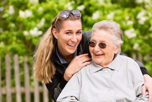 sitzende ältere Frau, dahinter weibliche Pflegekraft, die sich über die rechte Schulter beugt. Beide lachen und sind im Garten.