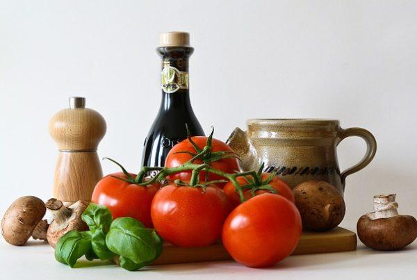 Tomate, Pilze und Basilikum auf einem Brett. Dahinter stehen Essig, Öl und eine Pfeffermühle.