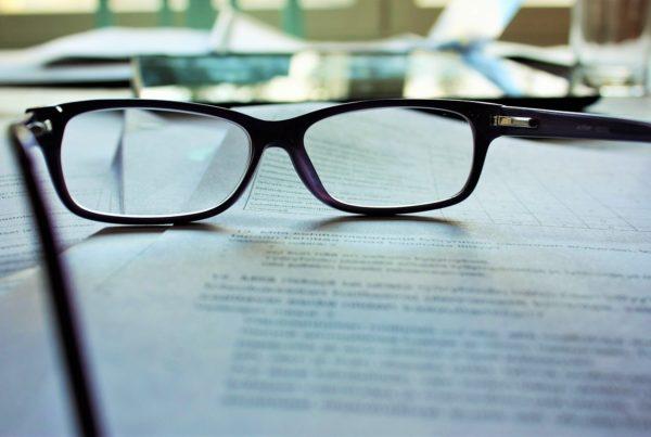 Zettel die auf einem Tische liegen. Auf den Zetteln liegt eine schwarze Brille.