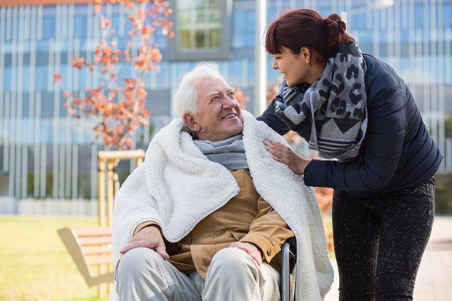 älterer Herr im Rollstuhl, der zugedeckt ist. Daneben Pflegekraft, die die Deckte zurechtrückt. Beide lachen sich gegenseitig an und sind im Freien.