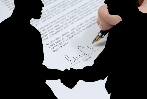 Im Hintergrund ein Vertrag der unterzeichnet wird.Im Vordergrund ein Schatten von zwei Personen, die sich die Hand schütteln.