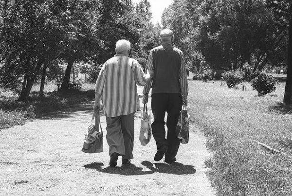 schwarz-weiß Foto von zwei älteren Herren, die auf einem Feldweg gehen. Der Rechte hat zwei Einkaufstüten in der Hand, der Linke hat in einer Hand eine Einkaufstüte und mit der anderen Hand hält er sich bei seinem Begleiter an.