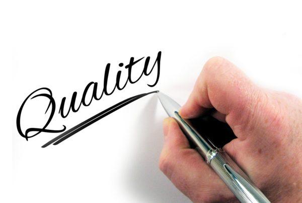 """auf einem Blatt Papier steht groß """"Quality"""". Hand, die mit einem Stift das Wort gerade unterstreicht."""