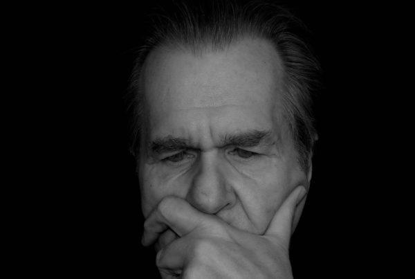 älterer Herr, der seine Finger auf den Mund gelegt hat und nachdenkt.